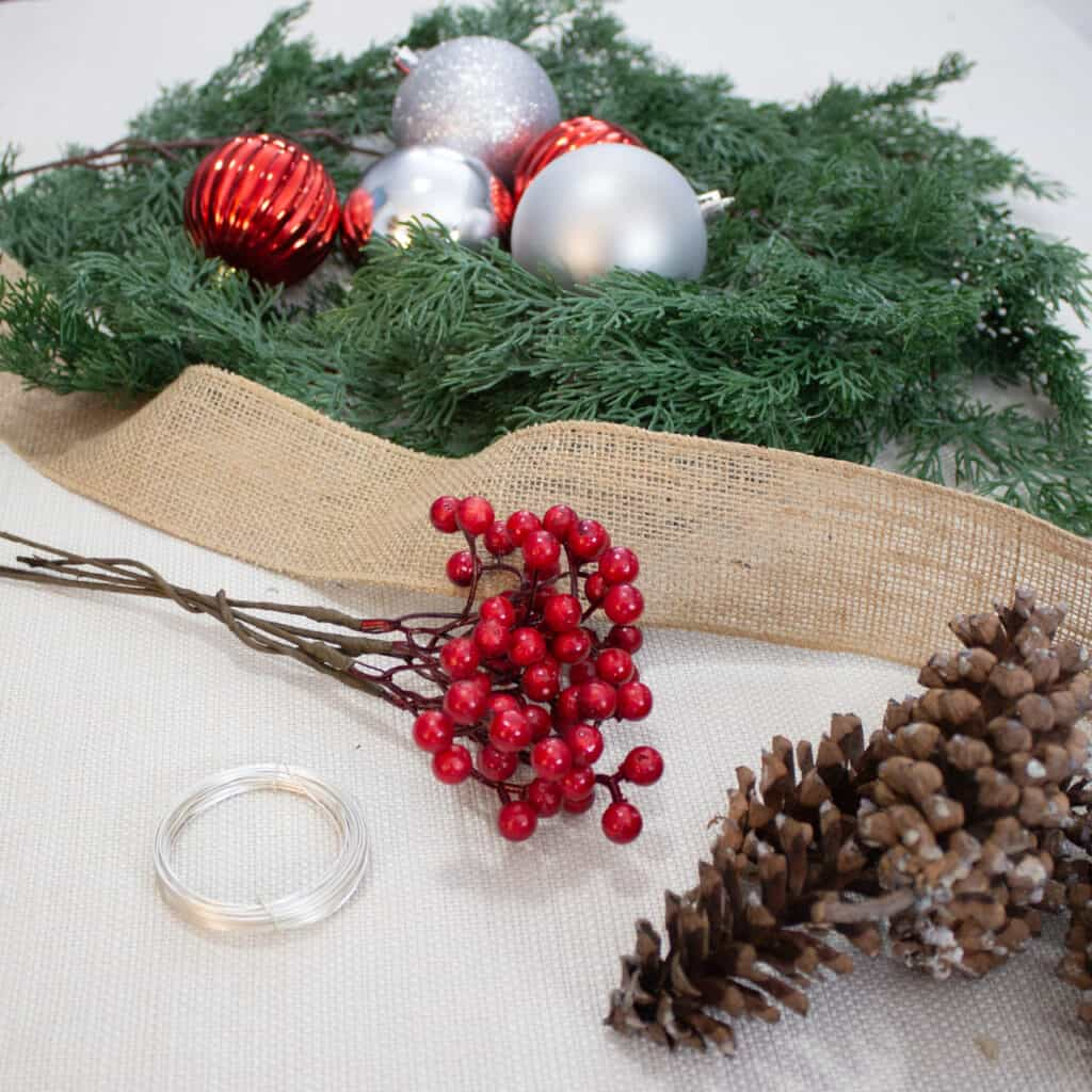 Pinecones, ornaments, fake berries, wire, ribbon and fake garland set out to add detail to a simple garland.