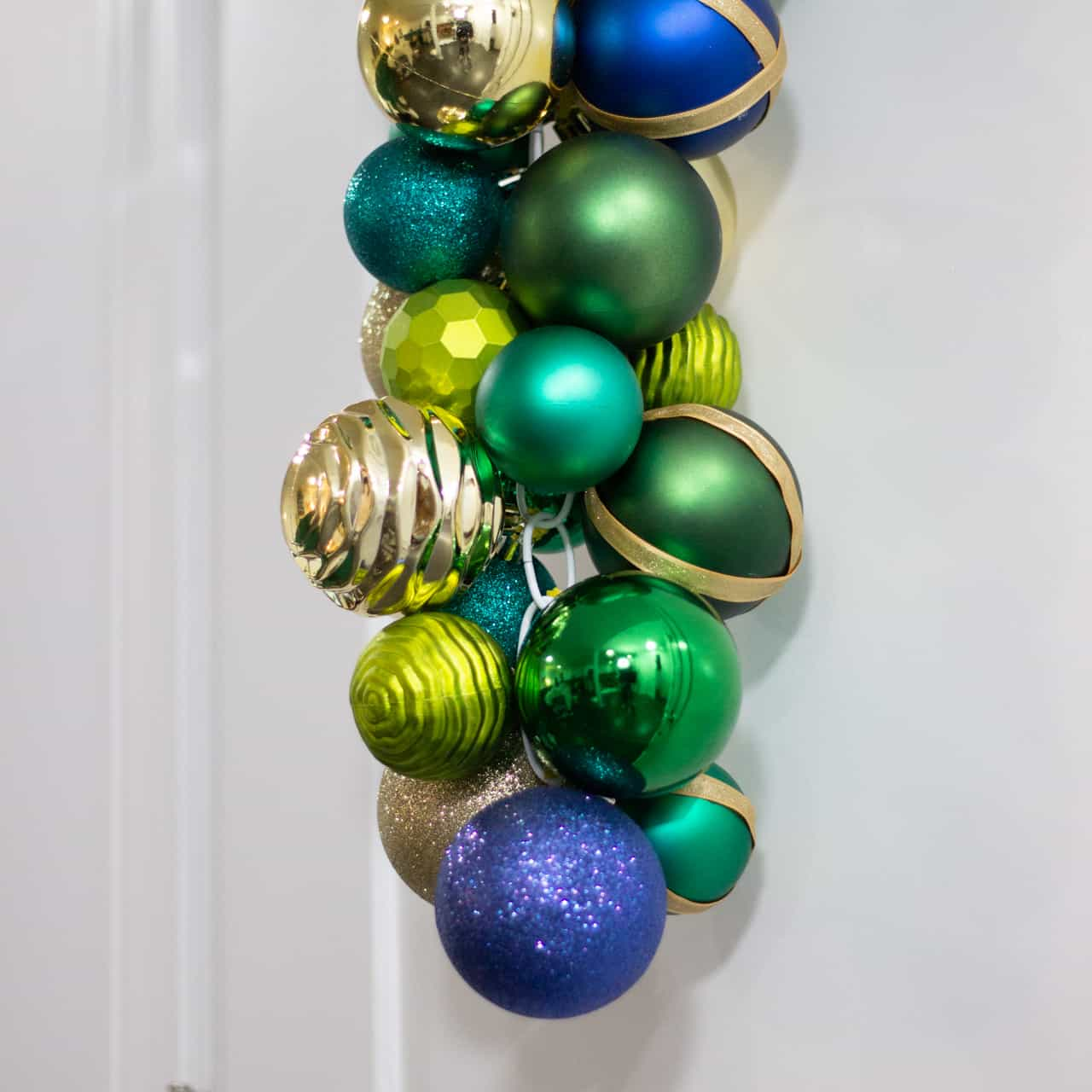 Blue, green, and gold ornaments hung on a white door.