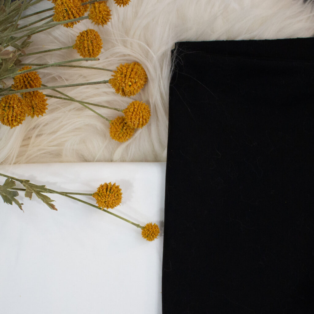 image of black and white cotton fabric on top of a wool throw and accented by yellow flowers