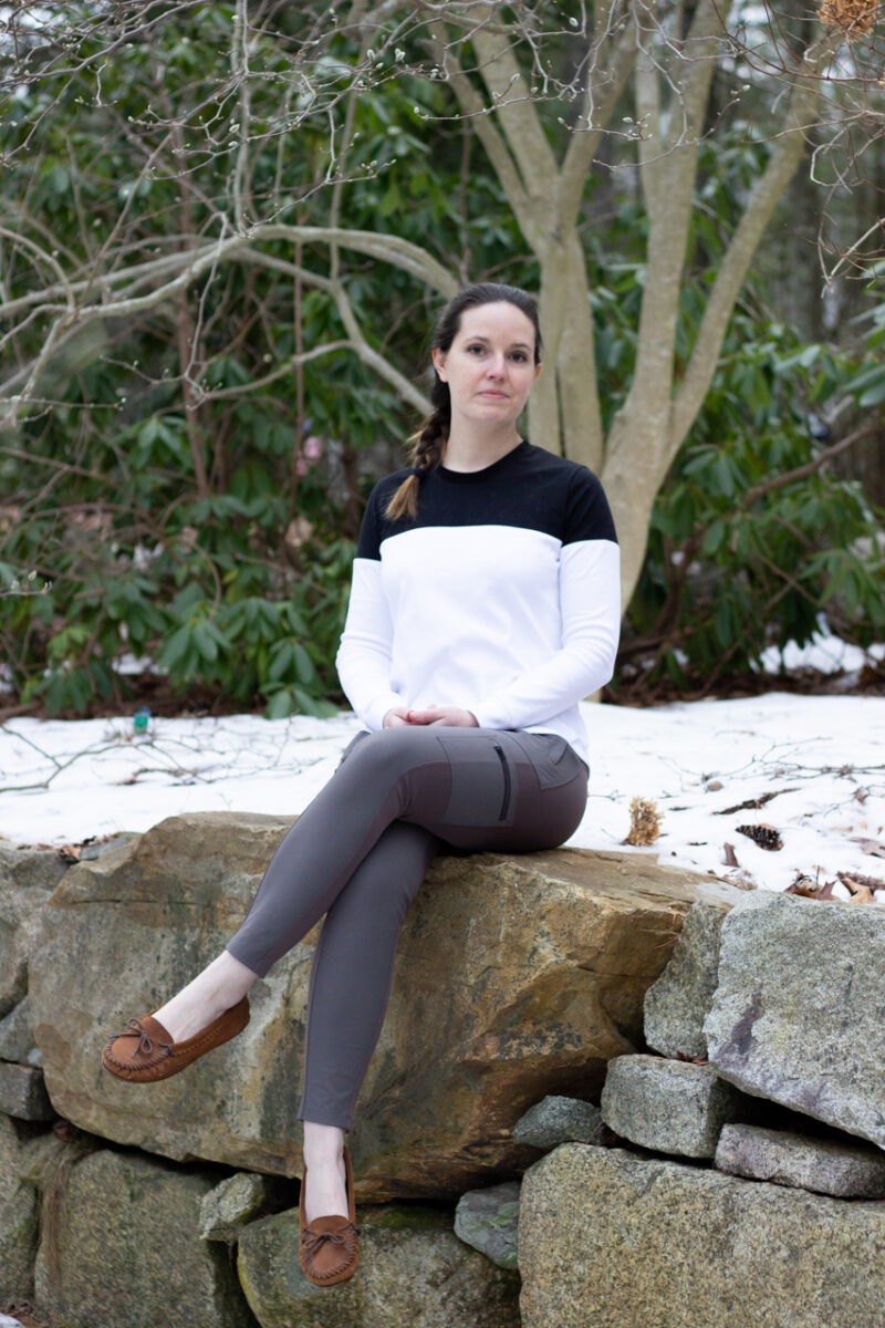 Sarah is sitting on a rock wearing her newly finished ensis tee